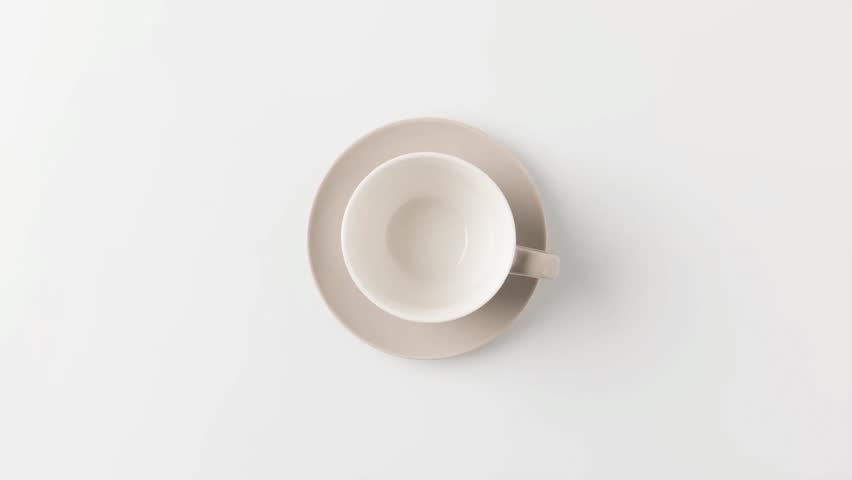 Stop motion footage of coffee preparing in cup on white tabletop