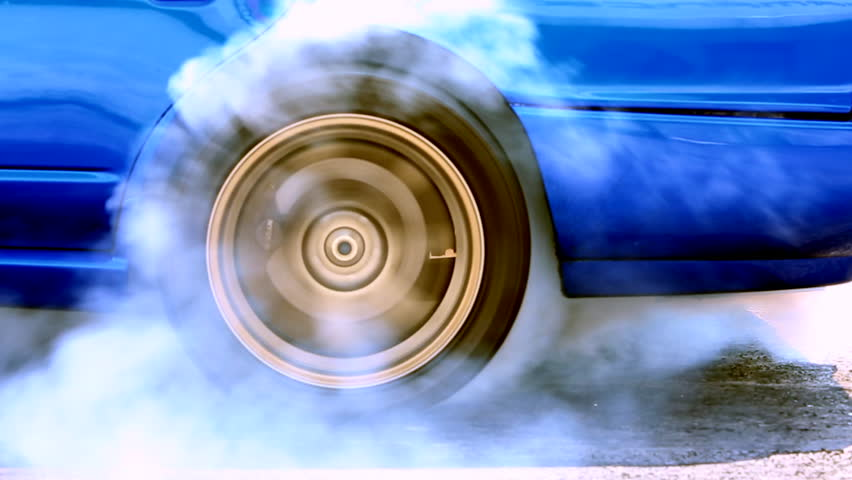 Acceleration detail car spinning wheel and creating white smoke on asphalt street road, Automobile and automotive drag car burnout tire rubber prepare for race or drift, Close up.