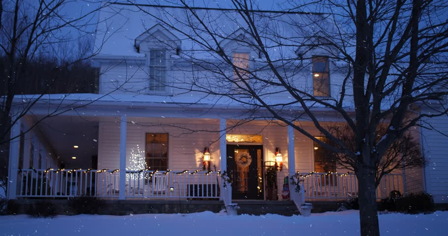 A nighttime low angle stationary winter establishing shot of an upscale Pennsylvania farmhouse decorated for Christmas. Bare trees. Snowing and clean versions.  | Shutterstock HD Video #1007303905