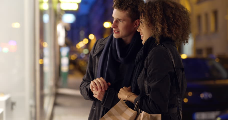 Attractive young couple window shopping in Paris. Caucasian male and African female admire window display in evening. 4k