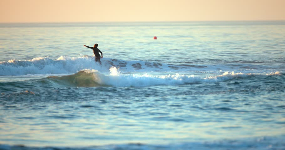 Silhouette of surfers at sunset   Shutterstock HD Video #1007333062