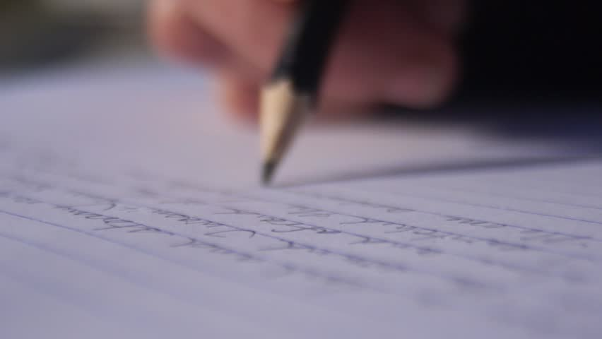 Close up of a female hand writing with a pencil on a notebook - Slow motion | Shutterstock HD Video #1007343649