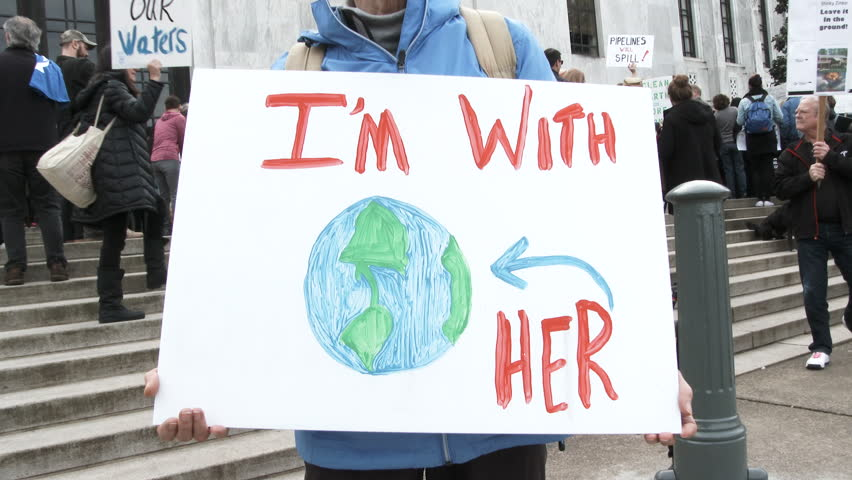 """SALEM, OREGON - FEBRUARY 2018: Woman holding sign at state capitol rally reading """"I'm With Her"""" in support of clean energy and to fight global warming."""
