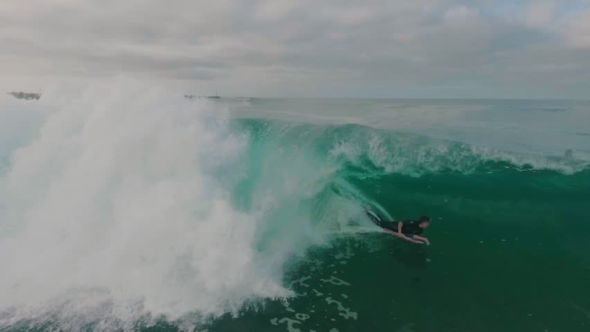 Aerial view of a boogie boarder riding a big wave deep in the barrel or tube.   Shutterstock HD Video #1007350246