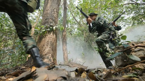 Squad of Fully Equipped and Armed Soldiers moving through Smokey Forest with Rifle Ready To Shoot in Slow motion.