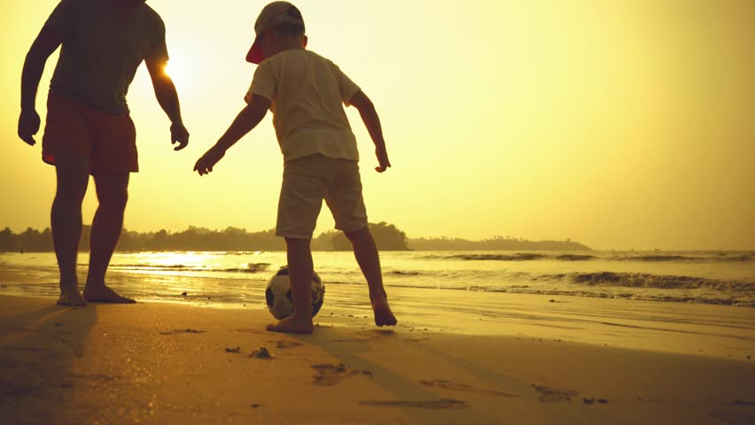 Father and son playing together with ball in football on the beach under sunset background | Shutterstock HD Video #1007368267