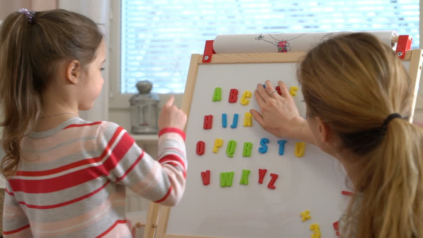 Home quarantine, distance learning. Little girl are learning to write letters with special desk. Young woman teaching her child the alphabet.