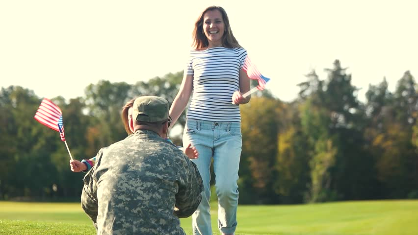 Back side view USA soldier in camoubackgrounde hugging with family. Embracing wife and daughter on the summer lawn.