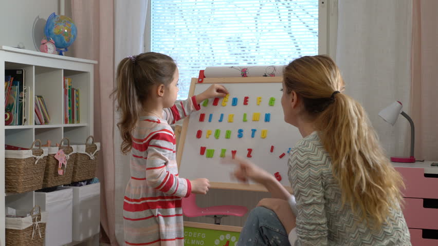 Distance learning at home. Little girl are learning to write letters with special desk. Young woman teaching her child the alphabet. Play and learn