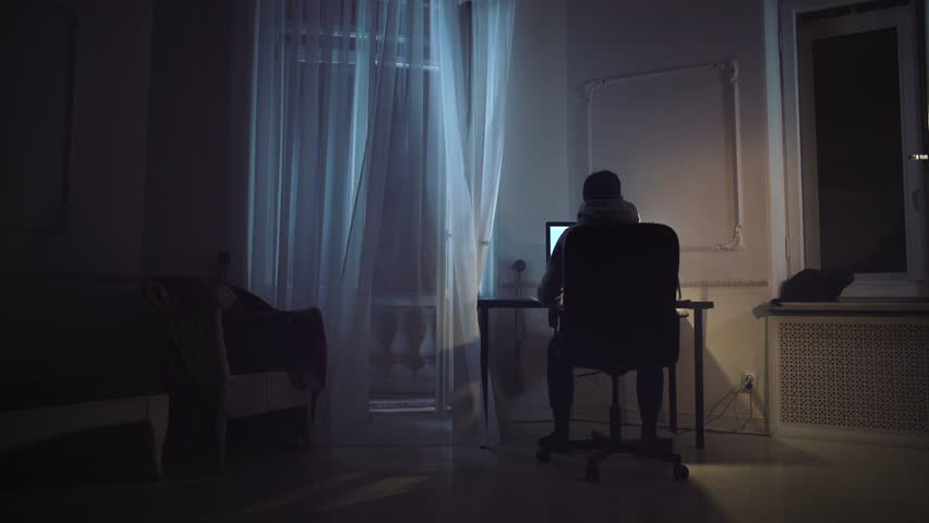 Young man working on screenplay on computer at night room, black cat on window sill, curtain shakes on wind