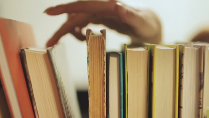 young woman choose books on shelf Royalty-Free Stock Footage #1007385853