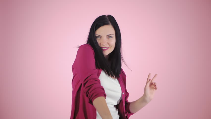 Fun dance workout. Portrait of young sporty woman in pink shirt dancing on colorful background. Slow motion.