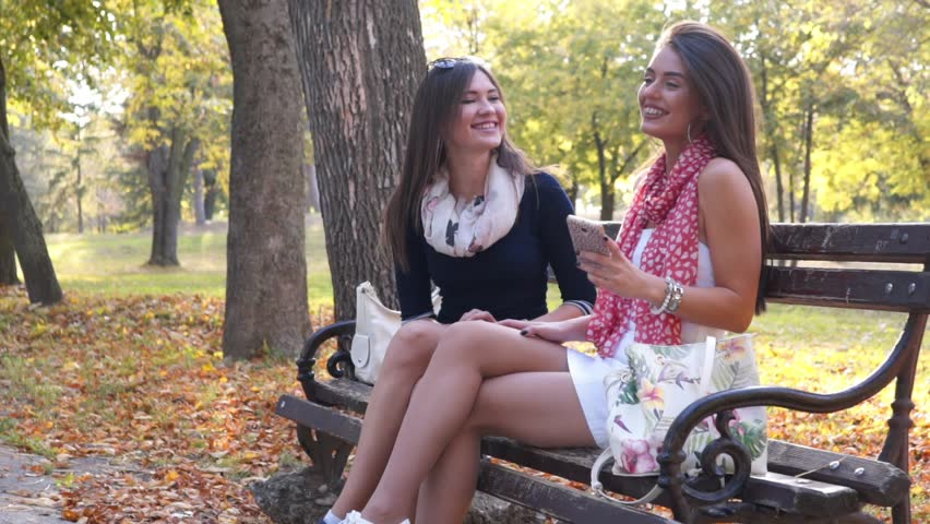 SLOW MOTION: Attractive girls looking at phone and laughing on bench | Shutterstock HD Video #1007399668