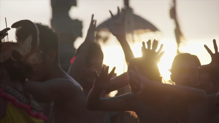 18 april 2016 Uluwatu, Bali, Indonesia. Balinese tradition performance kecak. People in silhouette wolking around in sunset light close-up heads and moving hands | Shutterstock HD Video #1007400676