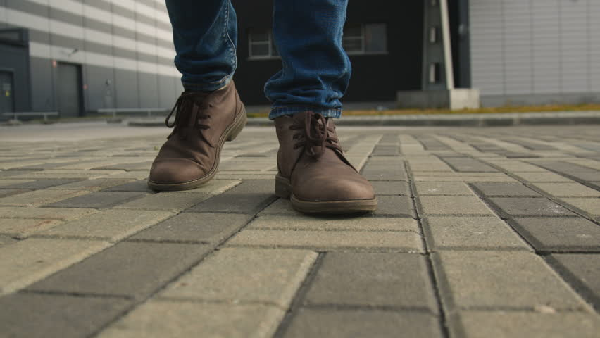 The one guy confidence walks along the town footway in jeans and stylish brown leather shoe. Point of view from first person on legs closeup. Spring cold weather, pedestrian go up front slow motion   Shutterstock HD Video #1007405065