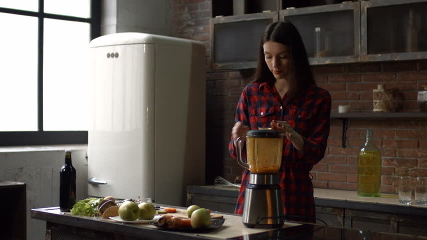 Stunning brunette woman blending food ingredinents with blender to make healthy detox smoothie in her kitchen. Attractive housewife preparing raw fresh juice using blender at home. Stabilized shot. | Shutterstock HD Video #1007407291