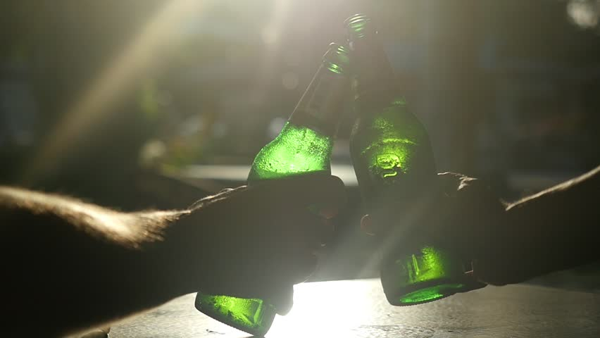Close up of friends taking bottles of the beer are clinking through the sun with lens flare effects in cafe while sun is going down. 1920x1080 #1007410825