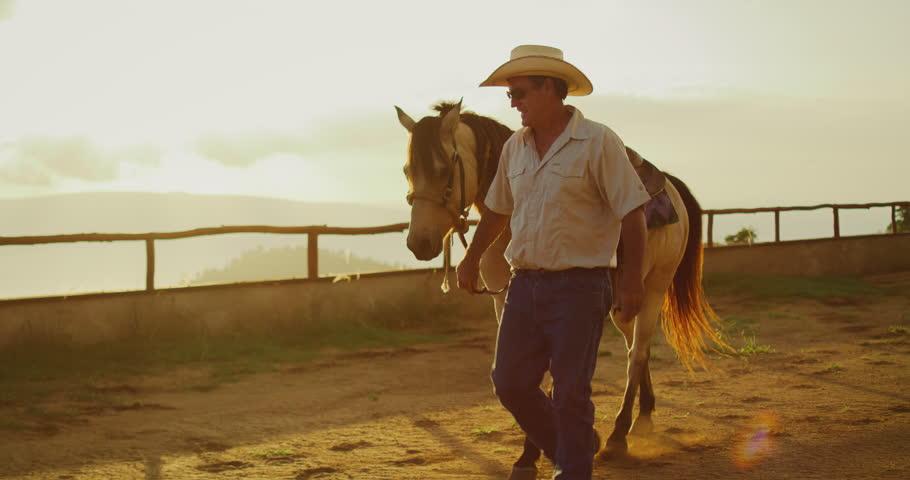 Cowboy walking his horse at sunset