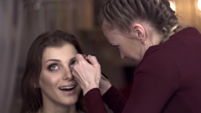 make-up artist paints eyelashes to a beautiful girl in a beauty salon