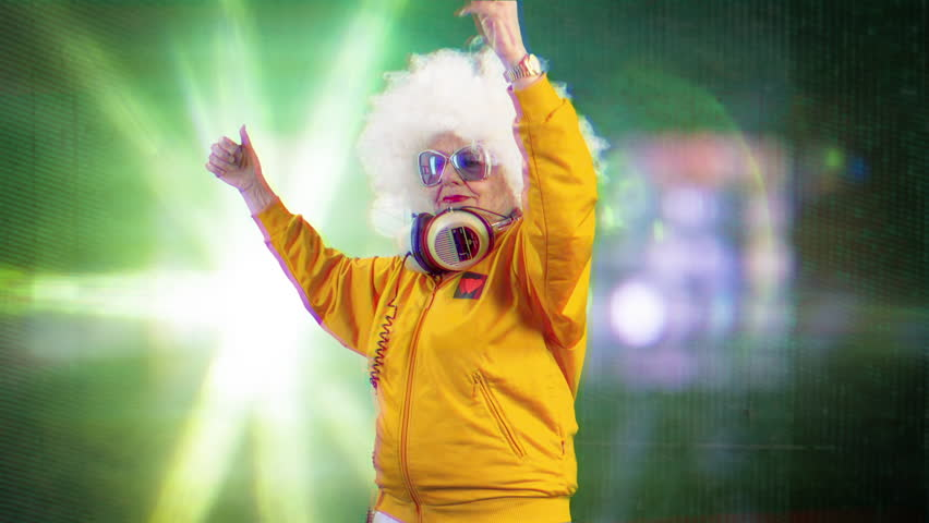 An amazing grandma disco dancer and dj, older lady partying in a hypnotic colourful disco setting.   Shutterstock HD Video #1007433364