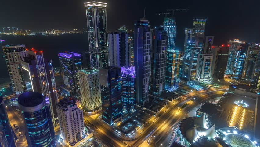 The skyline of the West Bay area from top in Doha timelapse, Qatar. Illuminated modern skyscrapers aerial view from rooftop at night. Traffic on the road | Shutterstock HD Video #1007434543