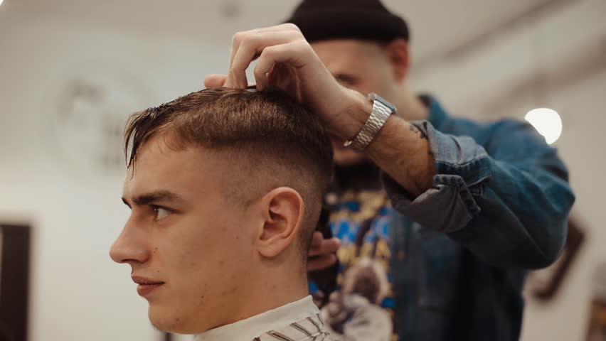 Male haircut with electric razor. Close up of man hair cut. Male hands barber shaving man with electric razor in barbershop. Barber cutting hair with hair trimmer. #1007441038