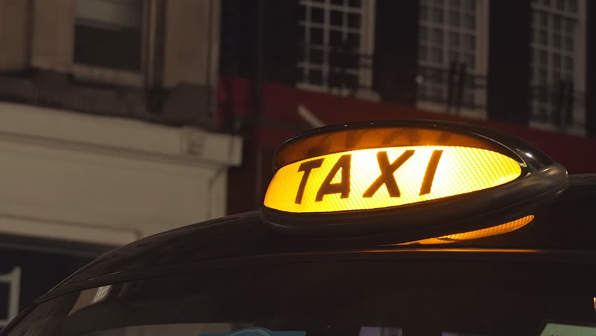 A taxi sign on a black cab. London at night.