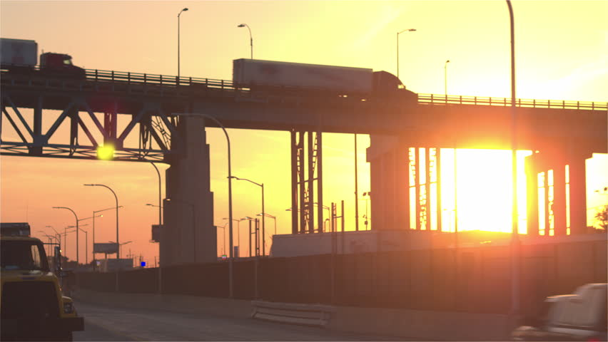 CLOSE UP: Freight container semi trucks driving from the distribution center storage depot to the busy multiple lane highway over a overpass bridge transporting goods at gorgeous golden light sunrise
