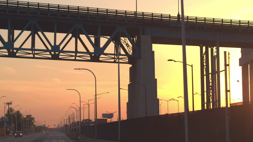 CLOSE UP, FPV: Cars driving along the multiple lane highway through the industrial town at gorgeous golden light sunset in Detroit city, USA. Traffic on the road through the commercial zone at sunrise