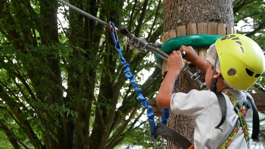 Boy walks on rope bridge in adventure park. | Shutterstock HD Video #1007452762