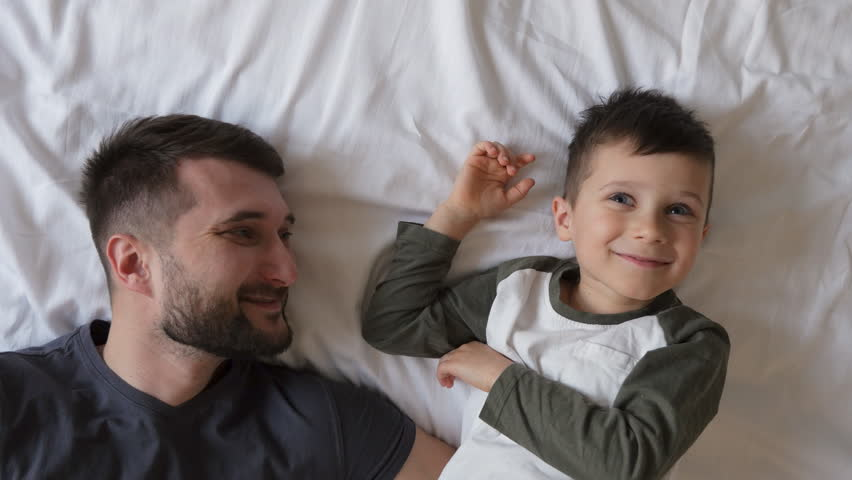 Bearded father with son lying on the bed | Shutterstock HD Video #1007454802