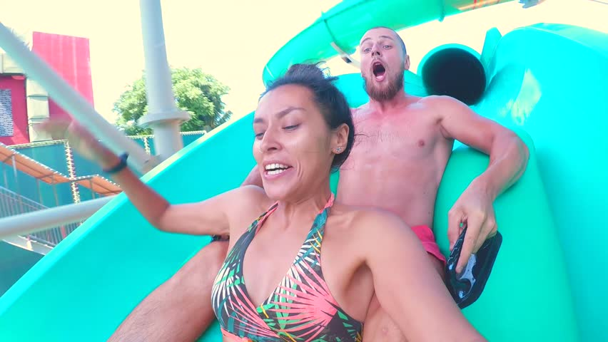 Young Mixed Race Couple Having Fun Riding Down Water Slide Tube and Making Selfie with Gopro Camera. HD Slowmotion.