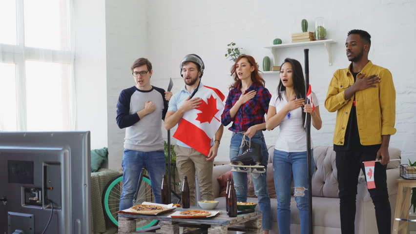 Multi ethnic group of friends listening and singing national Canadian anthem before watching sports championship on TV together at home