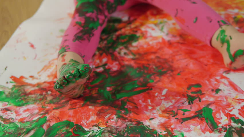 Closeup of a little girl, dirty in multicolored paints. The child learns to draw with finger paints | Shutterstock HD Video #1007482804