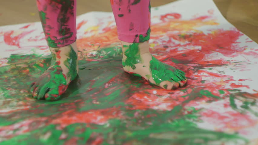 Closeup of a young child's foot gouache stained in paint. The child walks on a large sheet of white paper.