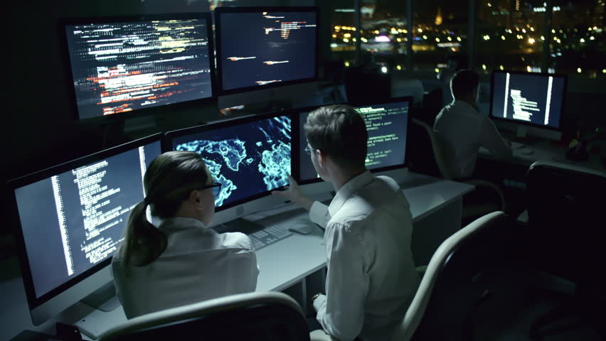 Tilt up of man and woman sitting in dark office at night and discussing program code and holographic world map on multiple monitors #1007484823
