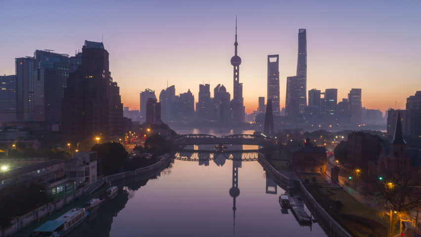 Panoramic Shanghai Skyline Silhouette at Dawn. Lujiazui Financial District and Huangpu River. China. Aerial Hyper Lapse. Drone is Flying Upward and Forward. Establishing Shot.