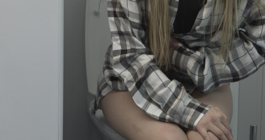 Low Section Of Woman Sitting On Toilet Bowl In Bathroom