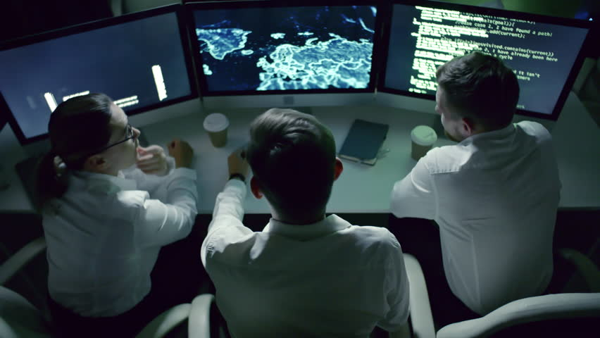 High angle view of professional team of IT security specialists speaking in front of computer monitors in dark office at night; computer code and holographic world map on display