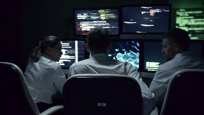 Rear view of three IT specialists discussing cyber security at desk in front of multi-display workstation in dark office at night #1007490898