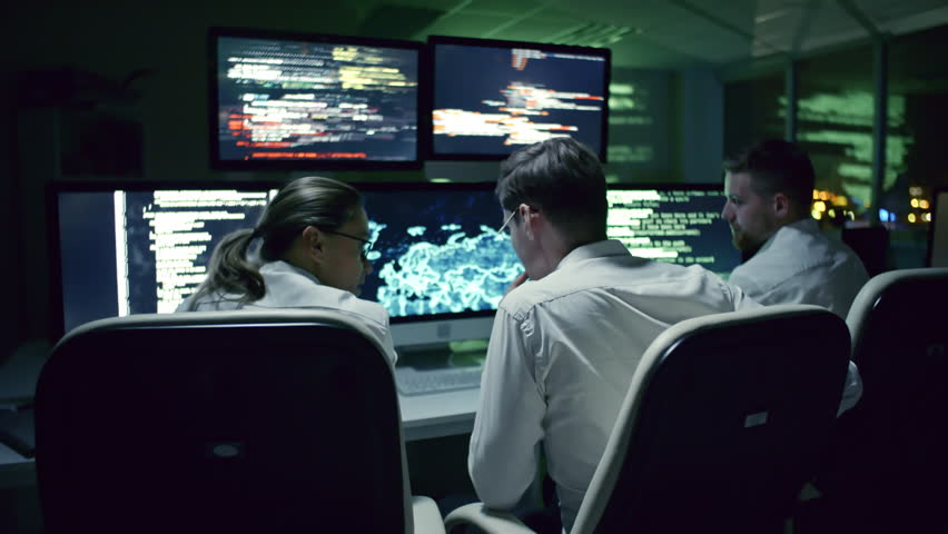 Rear view of three cyber security specialists talking at desk in front of multi-display workstation in dark IT office at night