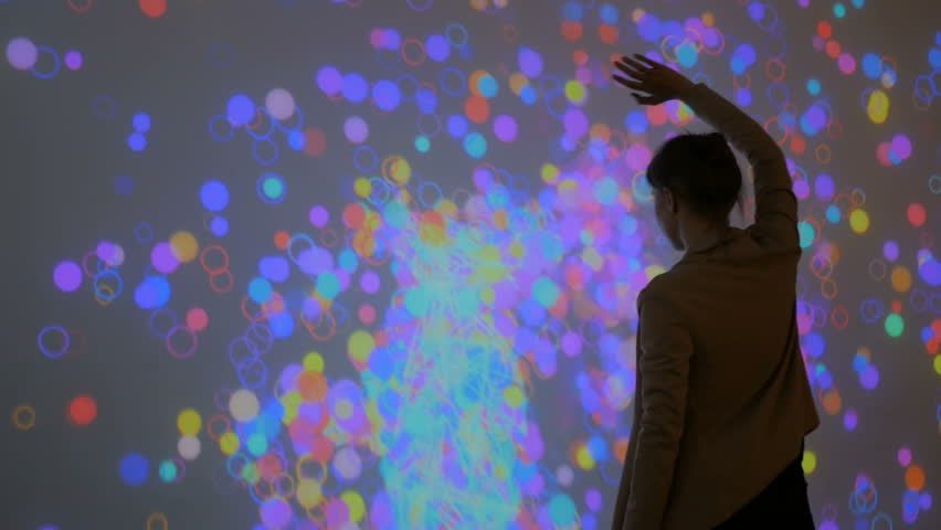 Large screen augmented reality experience - woman waving her arms in front of display. Science, future and technology concept