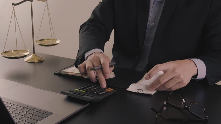 Justice and law concept.Male lawyer in the office working with calculator and bills with brass scale on wooden table | Shutterstock HD Video #1007500093