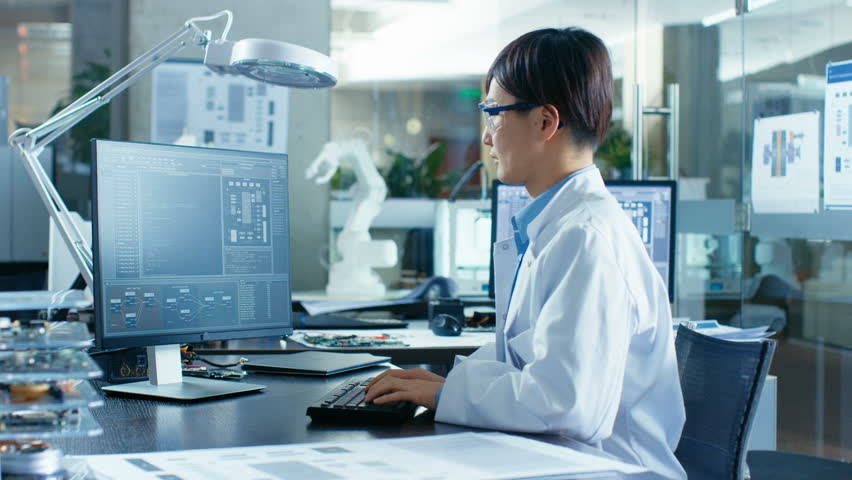 Asian Scientist Sitting at His Desk Doing Sophisticated Coding and Programming on His Desktop Computer. In the Background Computer Science Research Laboratory with Robotic Arm Model. 4K UHD.
