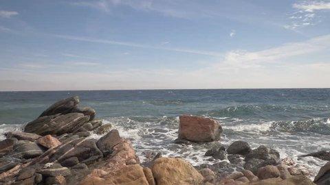Red sea coast line with splashy waves crashing to the shore stones near Taba city in Egypt.
