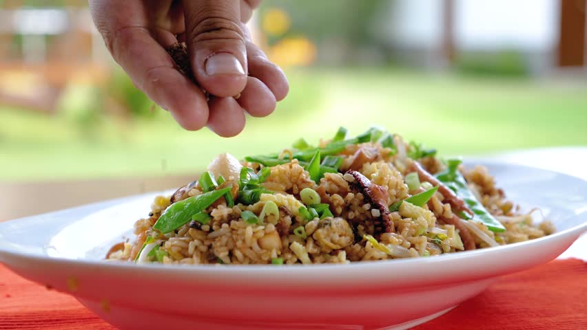 """Adding Sesame Seeds on a Fried Rice with Calamari. A Peruvian and Chinese food mixture called """"Chaufa de Mariscos""""."""