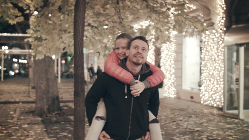 A happy family walks the evening in the city on holidays. The father carries on his back a daughter who tears a leaf from an autumn tree #1007519278