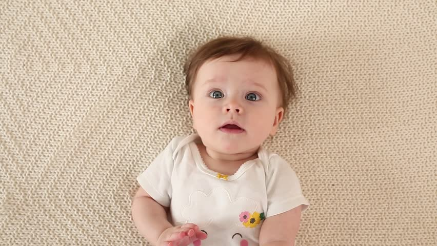 Top view and close-up portrait of cute adorable baby girl wearing white body in bedroom looking at camera. Newborn child relaxing and smiling in the bed in children nursery. Family morning at home