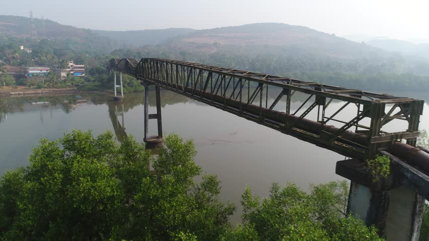 Flying along the long rusty aqueduct truss over the muddy river. Aerial view. | Shutterstock HD Video #1007525992