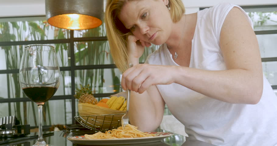 Bored depressed blond haired woman playing with her spaghetti dinner and drinking red wine